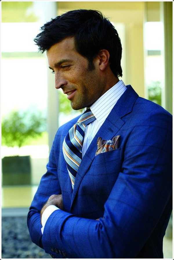 un traje azul con una corbata a rayas le dan un aspecto formal.